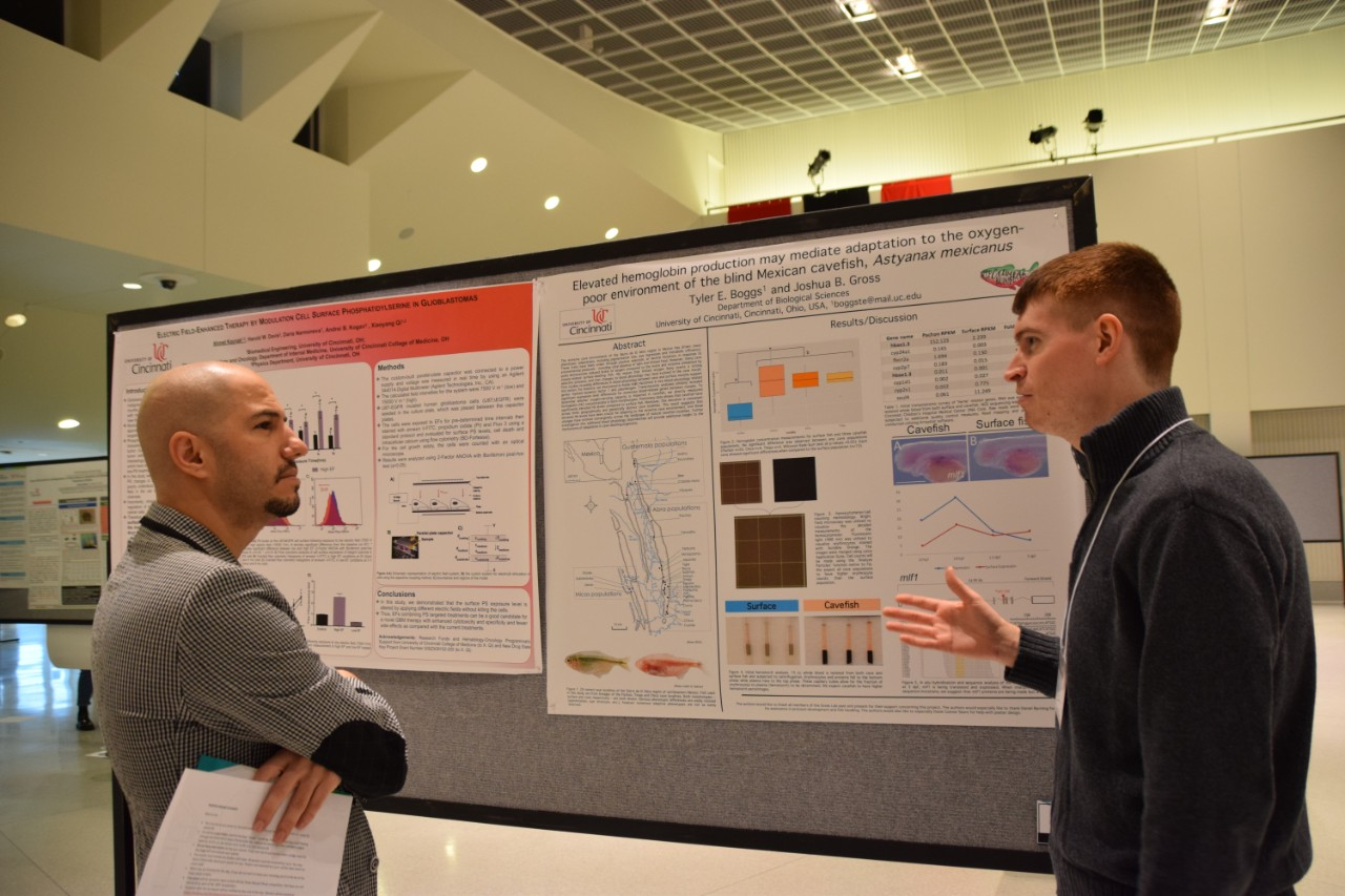 A student discusses his research and poster with a faculty judge.