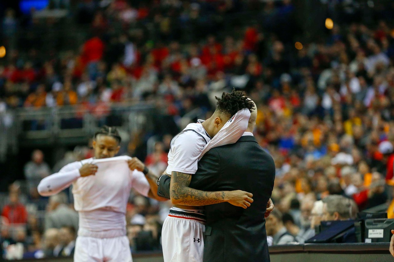Mick Cronin hugs Cane Broome as Broome and Justin Jenifer exit the court in the final seconds of the Bearcats' 79-72 loss to Iowa on Saturday, March 22