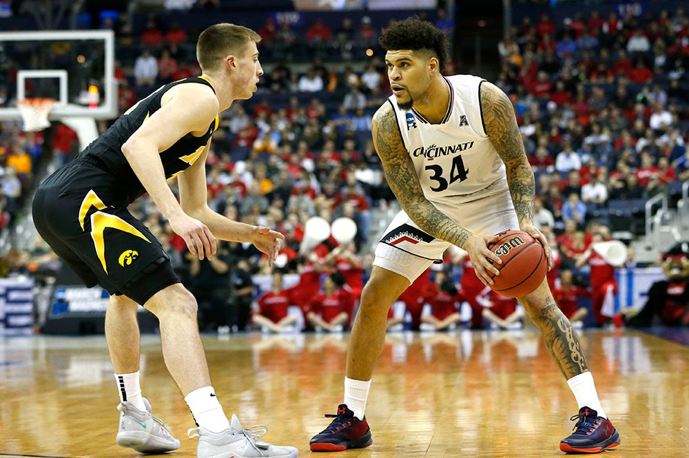 UC's Jarron Cumberland holding the ball while guarded by an Iowa player
