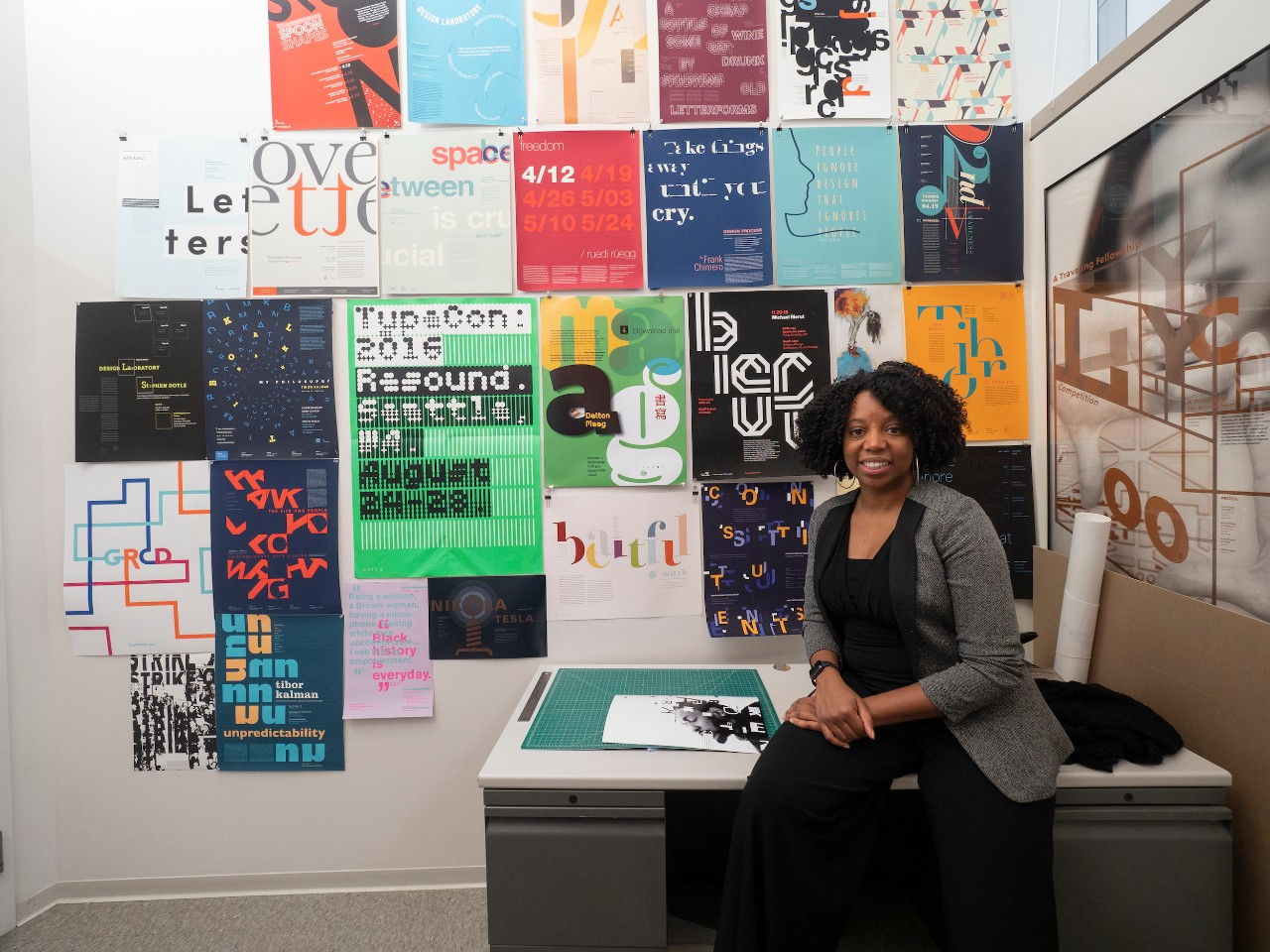Reneé Seward poses in her office in front of posters