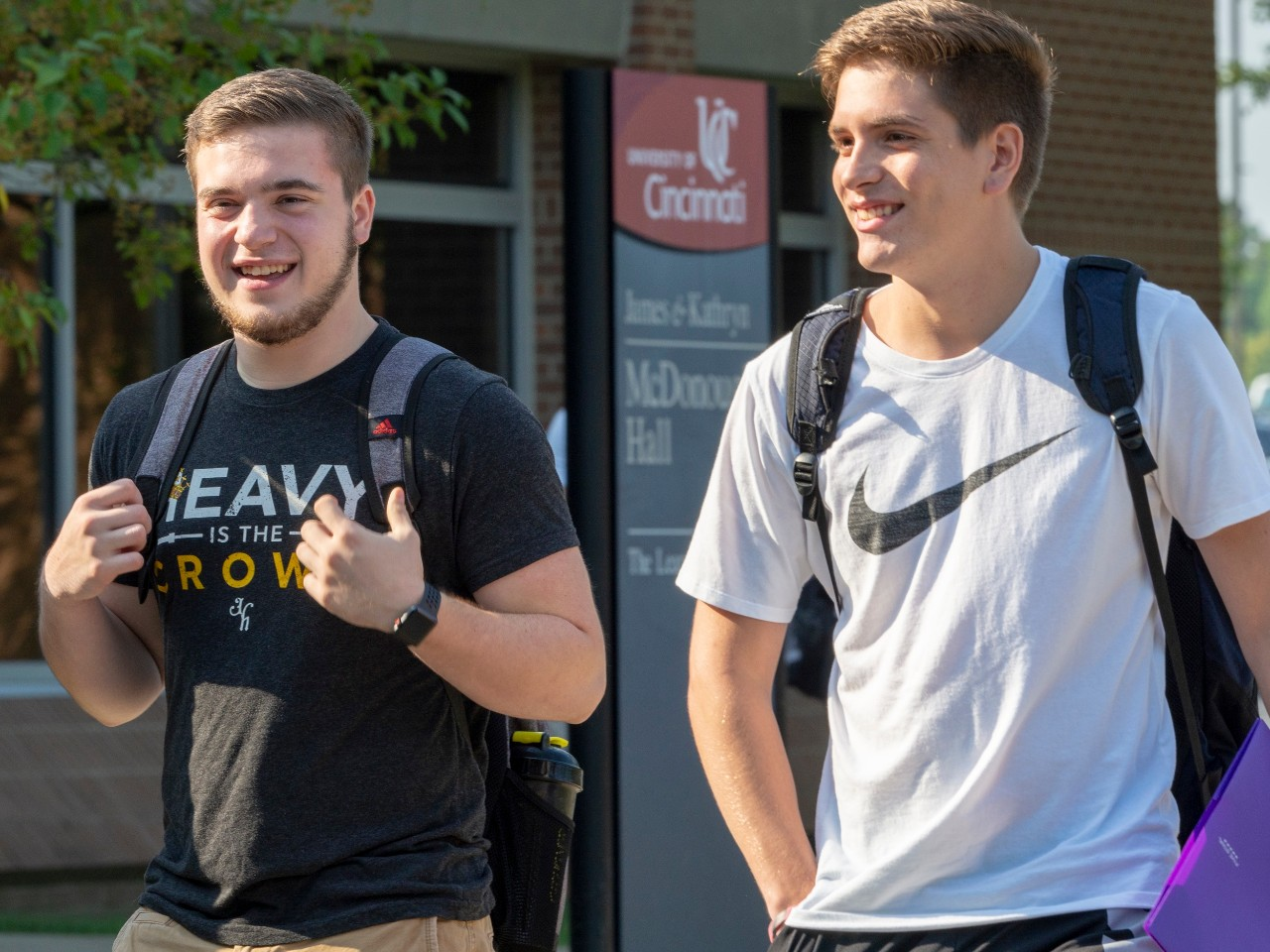 Male students walking across UC Clermont's campus