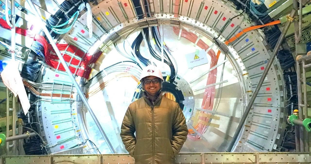 UC postdoctoral fellow Saurabh Sandilya stands in front of the Belle II detector in Japan's SuperKEKB collider.