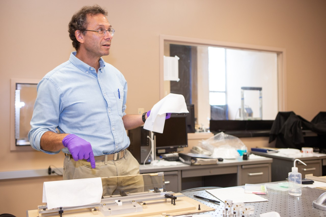 Alan Schwartz wearing rubber gloves points to a block of quartz in a clean room in his optics lab.