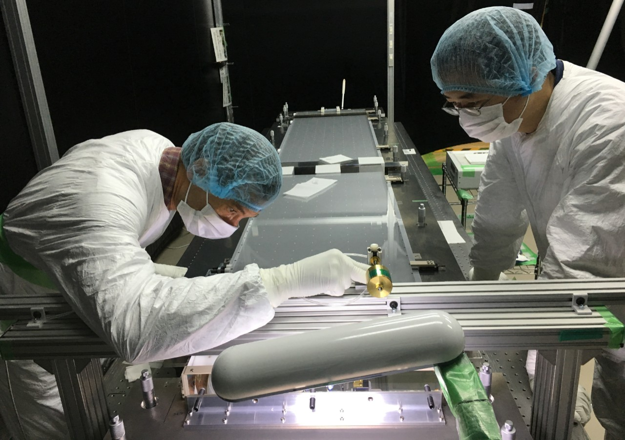 Researchers in protective clothing and surgical masks lean over a work table illuminated with harsh light.