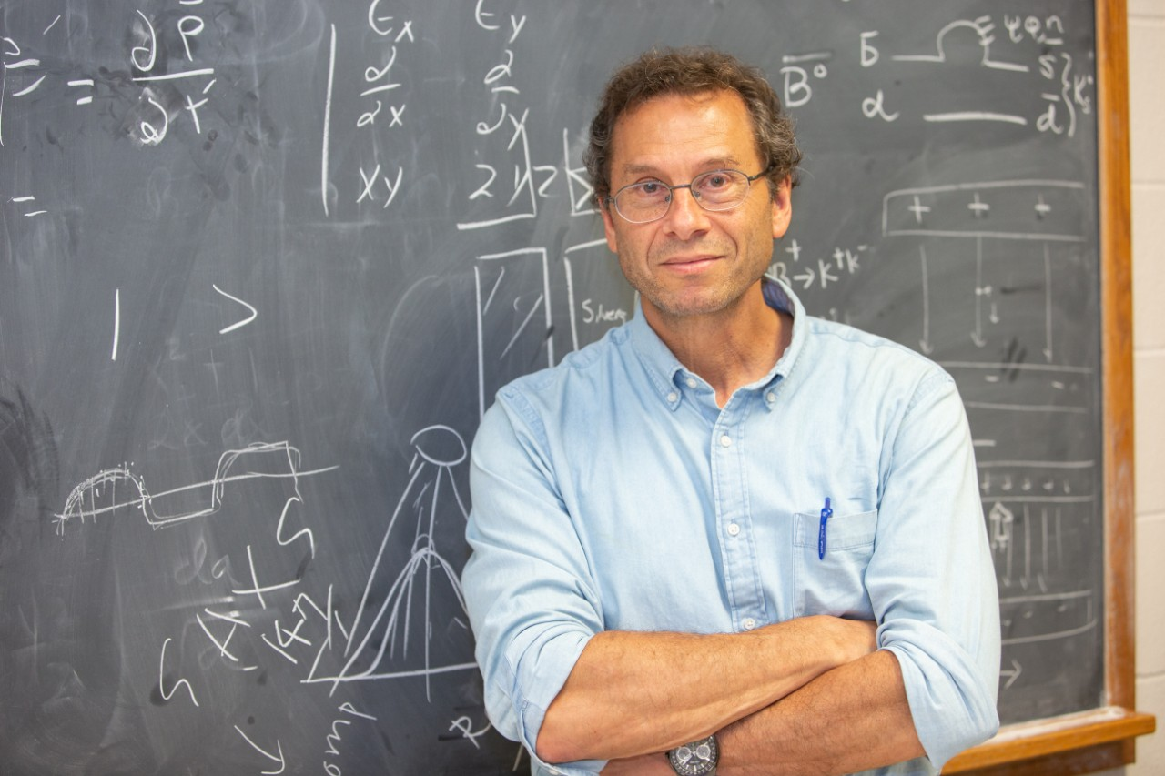 Alan Schwartz stands in front of a blackboard with equations scrawled in chalk behind him.