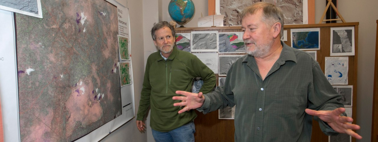 UC geography professors Nicholas Dunning and Christopher Carr stand at a large satellite map of their study area in the Yucatan Peninsula in Carr's office.