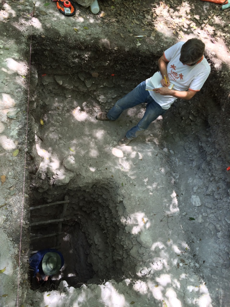 UC geography professor Nicholas Dunning is barely visible in a hole with a UC student standing above him at an excavation.