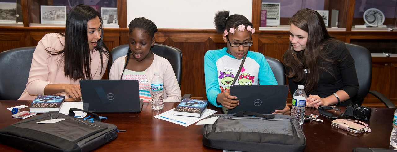 Two medical students shown with young mentees using laptops at UC College of Medicine.