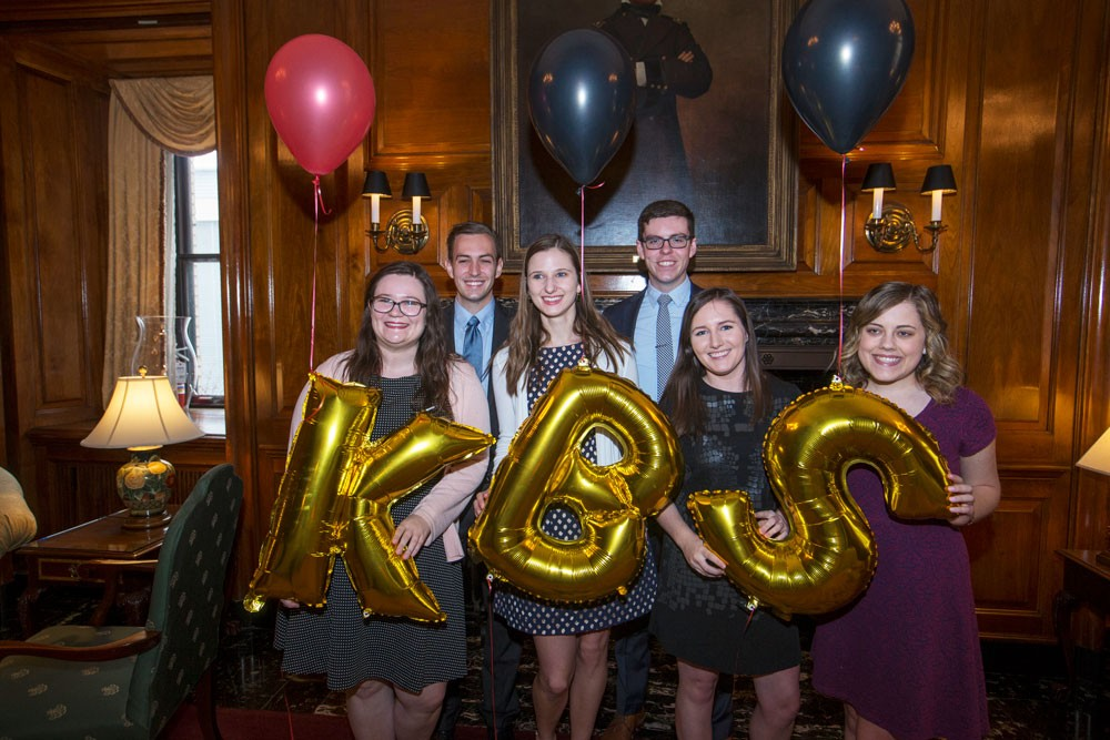 "Six business students, some of whom are holding metallic gold balloons in the shape of letters that spell ""KBS"""