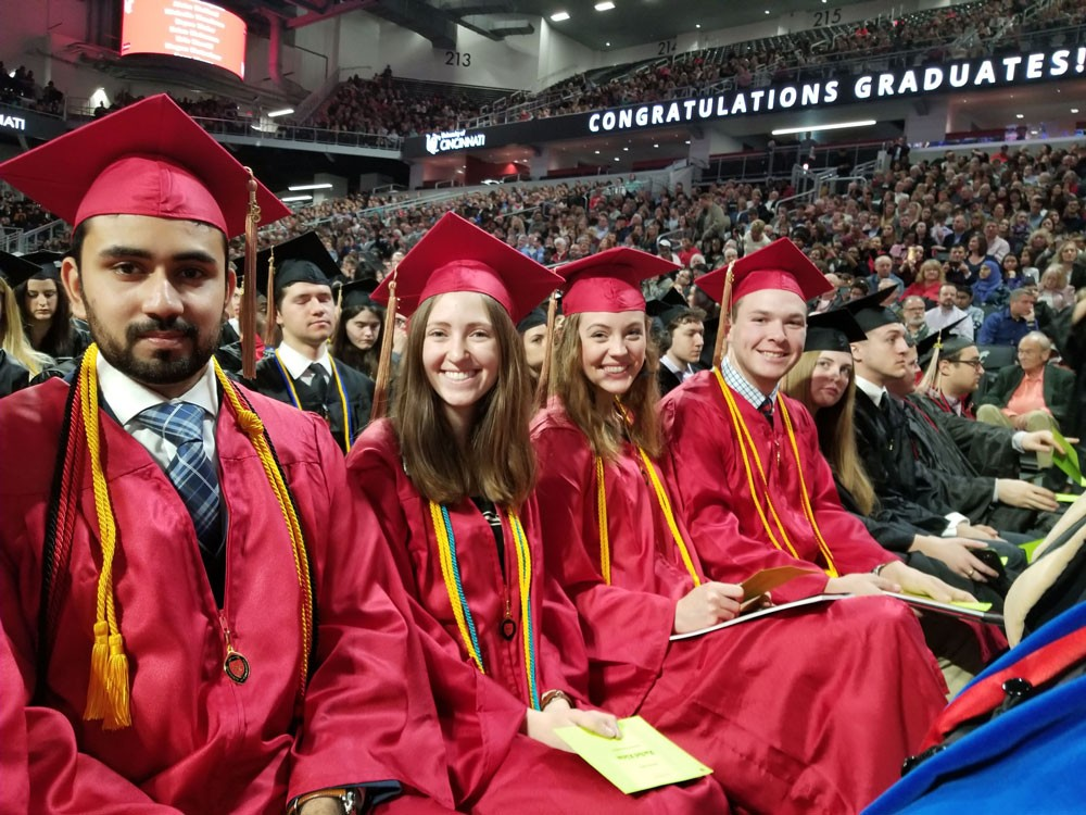 Students in red mortarboards and gowns sitting in Fifth Third Arena at a past commencement
