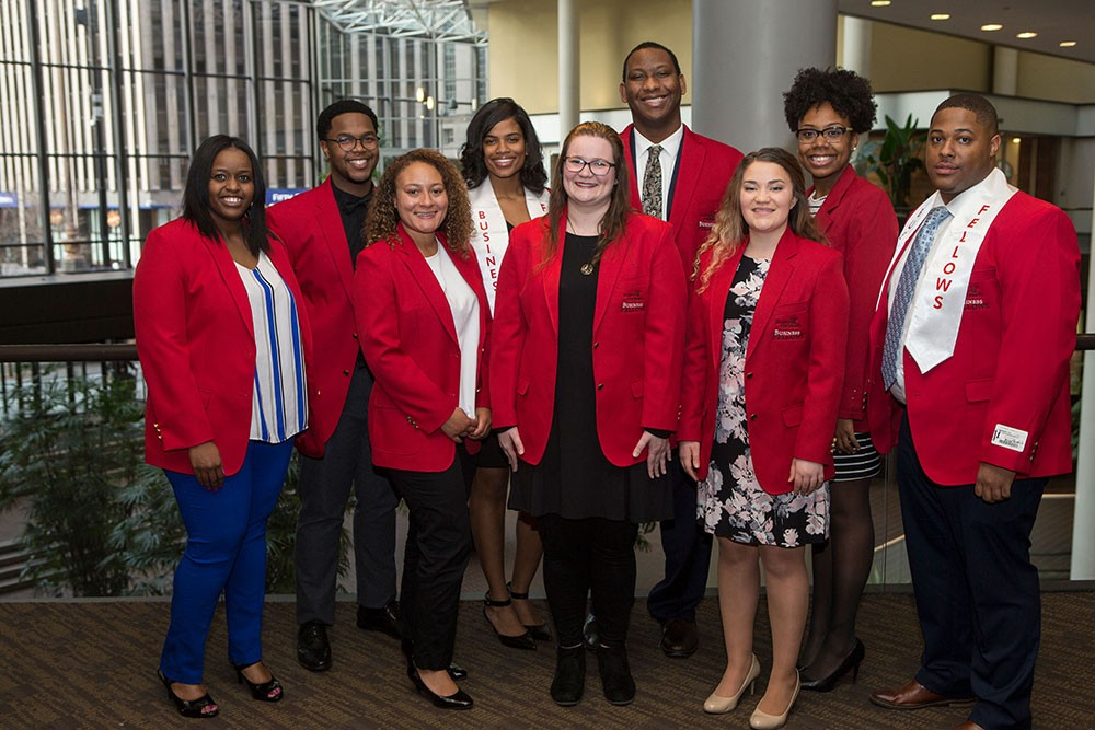 Nine students wearing red blazers posing for a photo