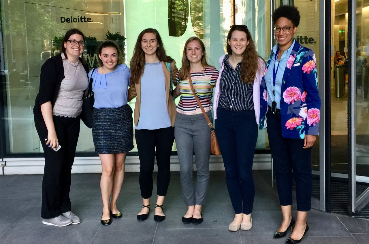 Six UC women stand outside a business front during their student co-ops.
