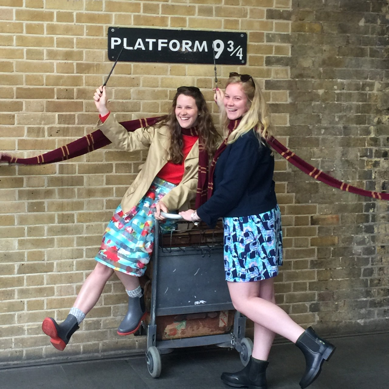 Two college women stand under a Platform 9 3/4 sign in London, England.