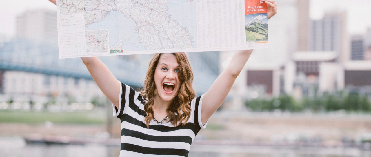 UC student Kendall Cappel holds up a map of Austria while she stands in front of buildings in Vienna.