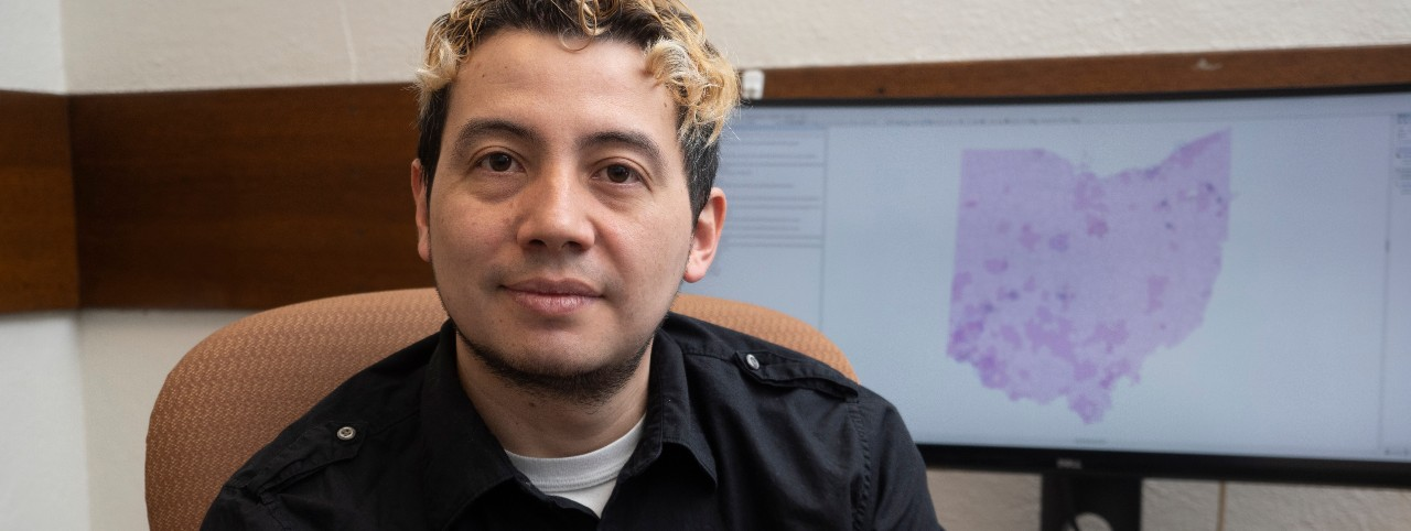 UC student Andres Hernandez poses in front of a computer screen with his Ohio opiate map.