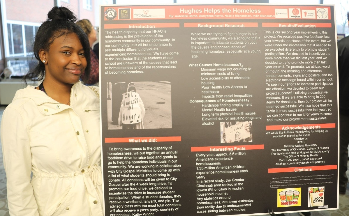 A Hughes High School student by her poster at the second annual Southern Ohio Scholars Day