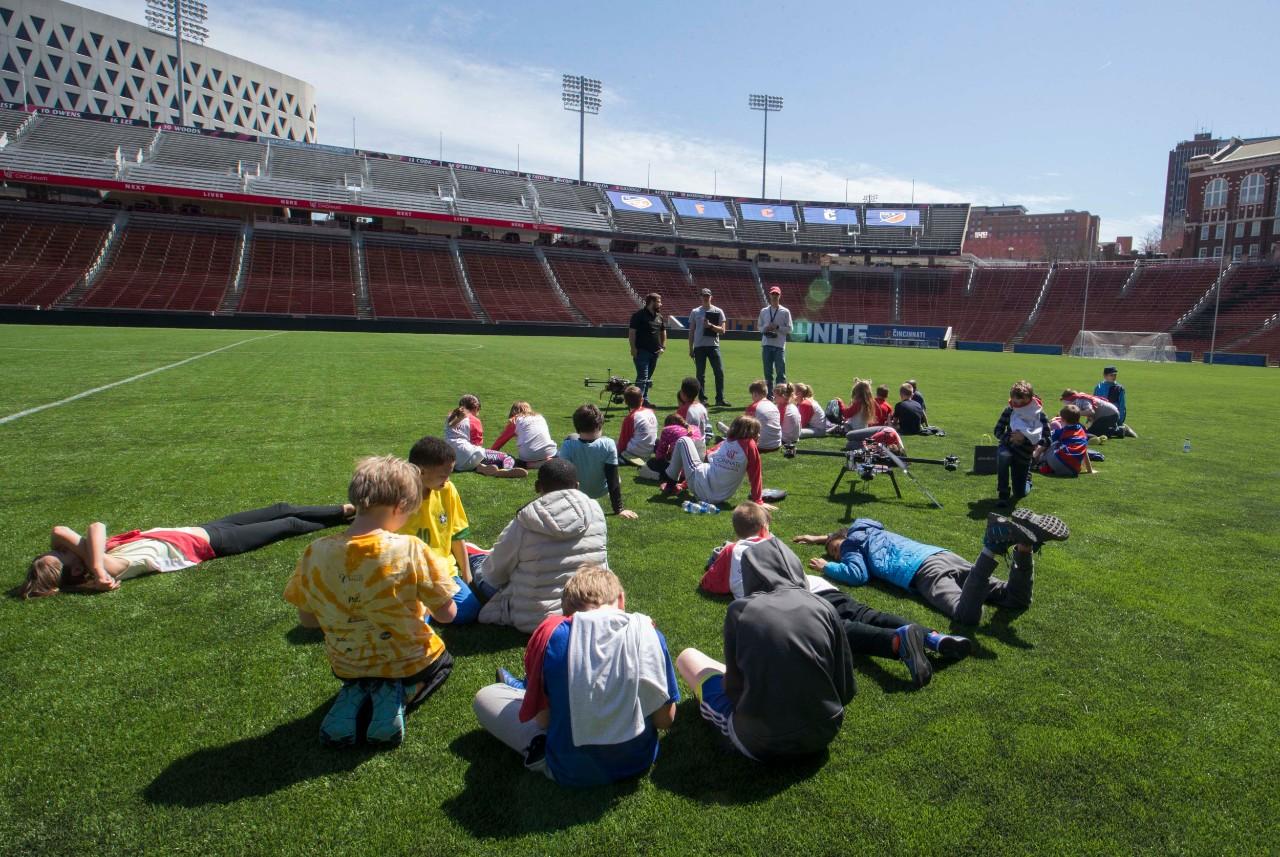 Elementary school children sit in Nippert Stadium watching a drone demonstration.