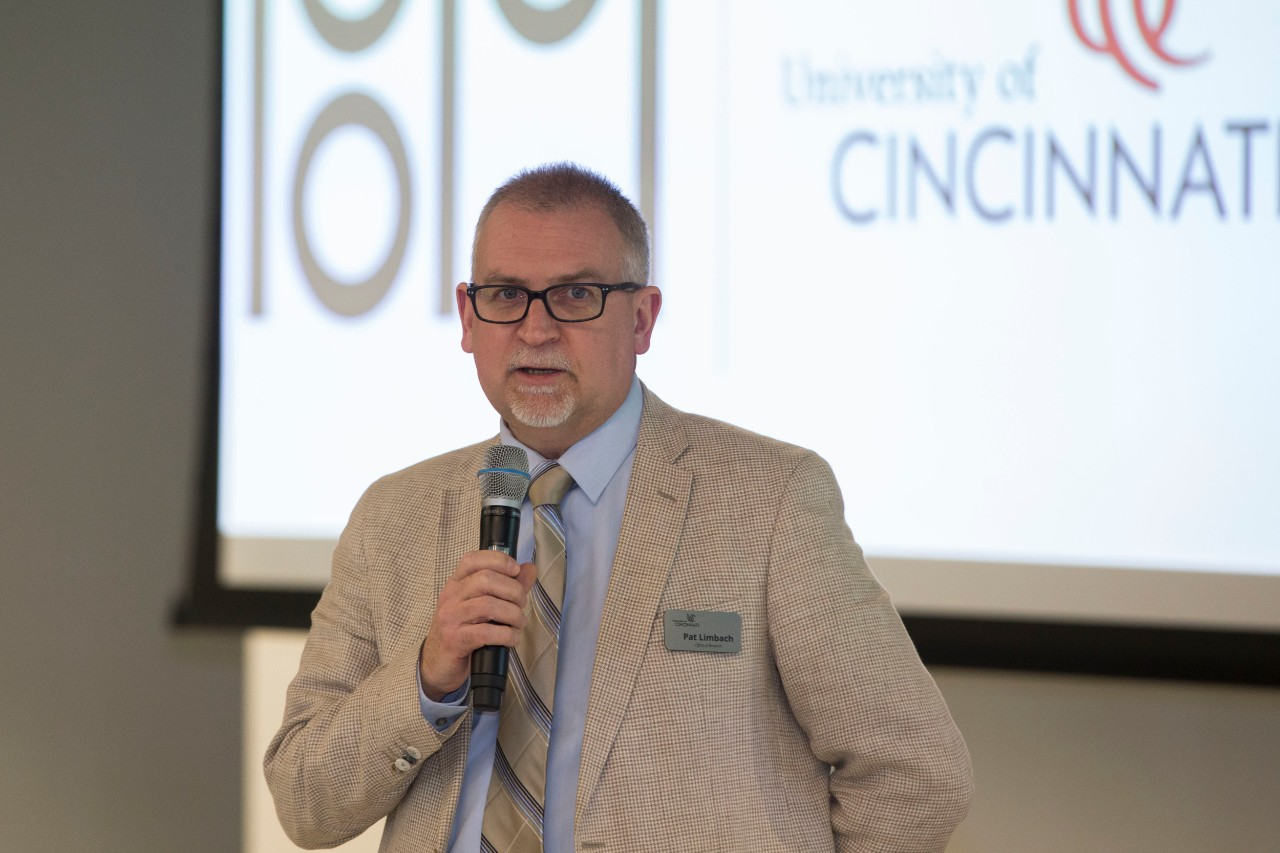 UC's Pat Limbach stands holding a mic while speaking to a crowd at the R&I Week Hutton Lecture.