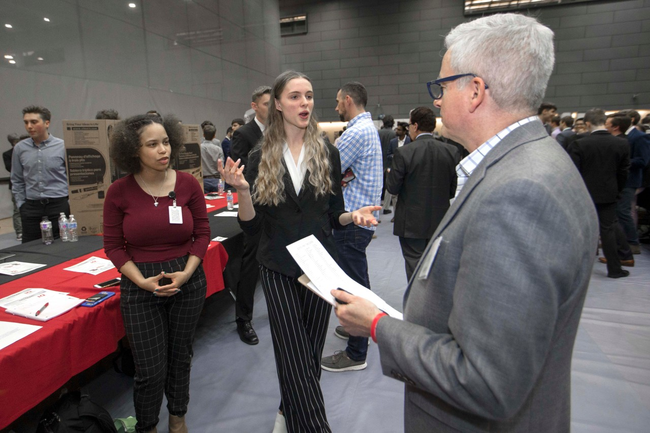 Two UC women give an Innovation Quest elevator pitch in Campus Rec Center during R&I Week.