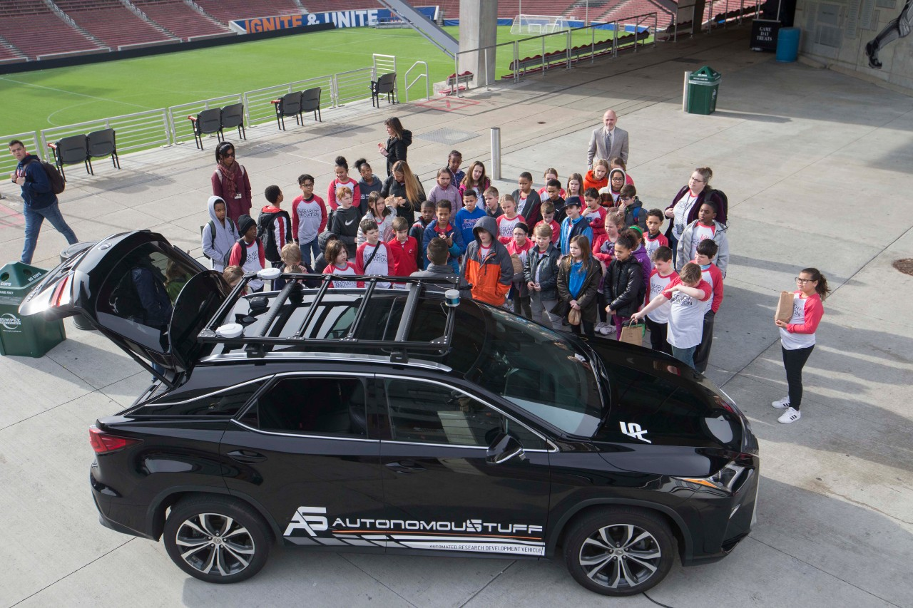 Elementary school children look inside an autonomous vehicle in UC's Nippert Stadium during R&I Week.