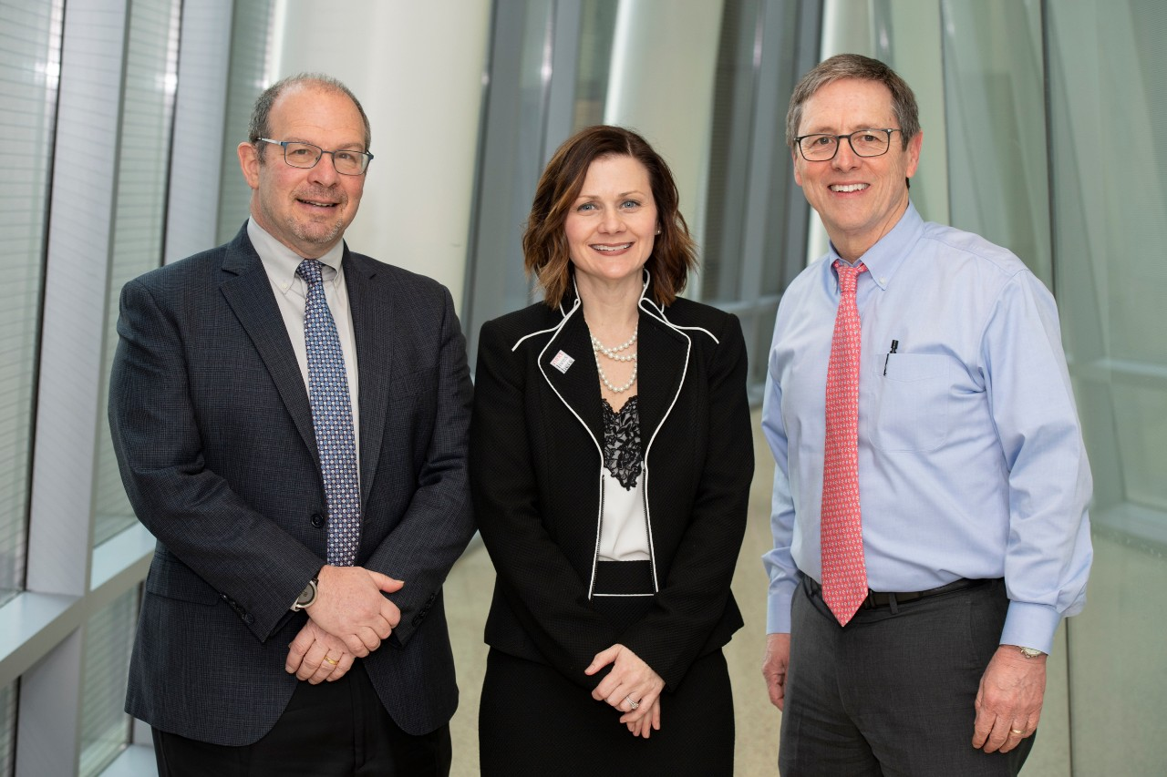 Two men and a woman stand in UC's College of Medicine during the R&I Week Hutton Lecture.