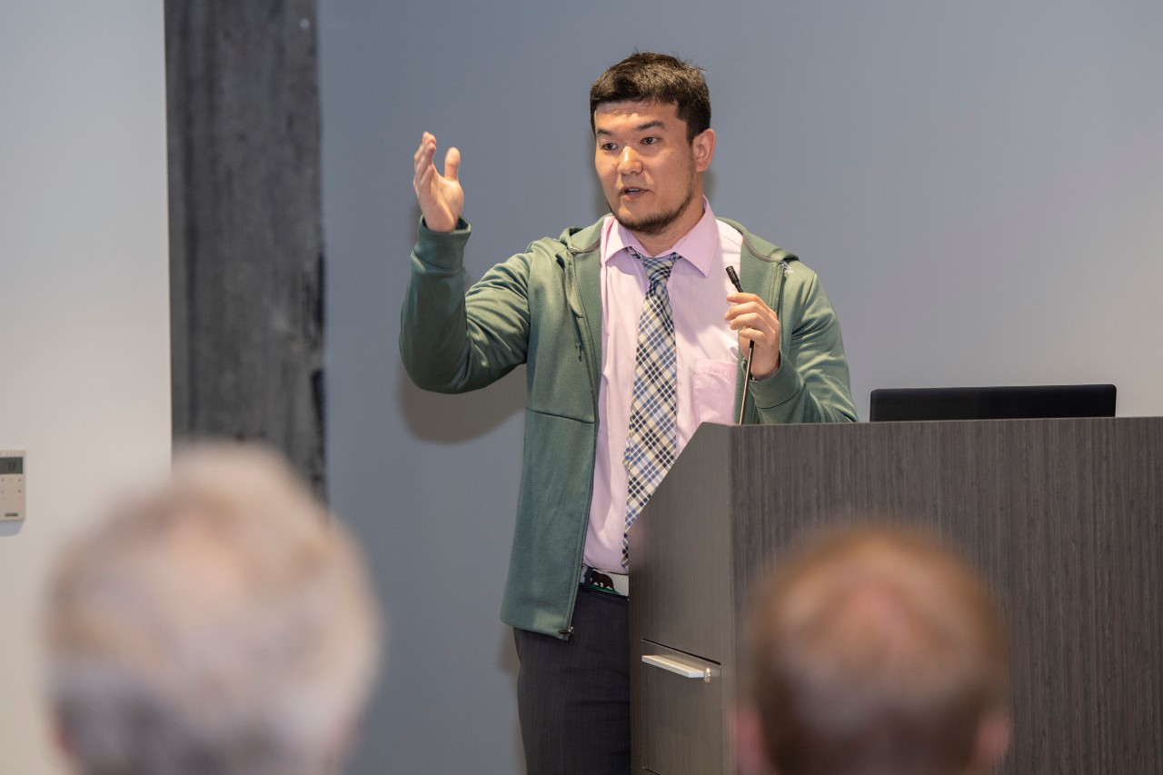 Man stands at a podium at UC's R&I Week discussing Cincinnati's opioid crisis.