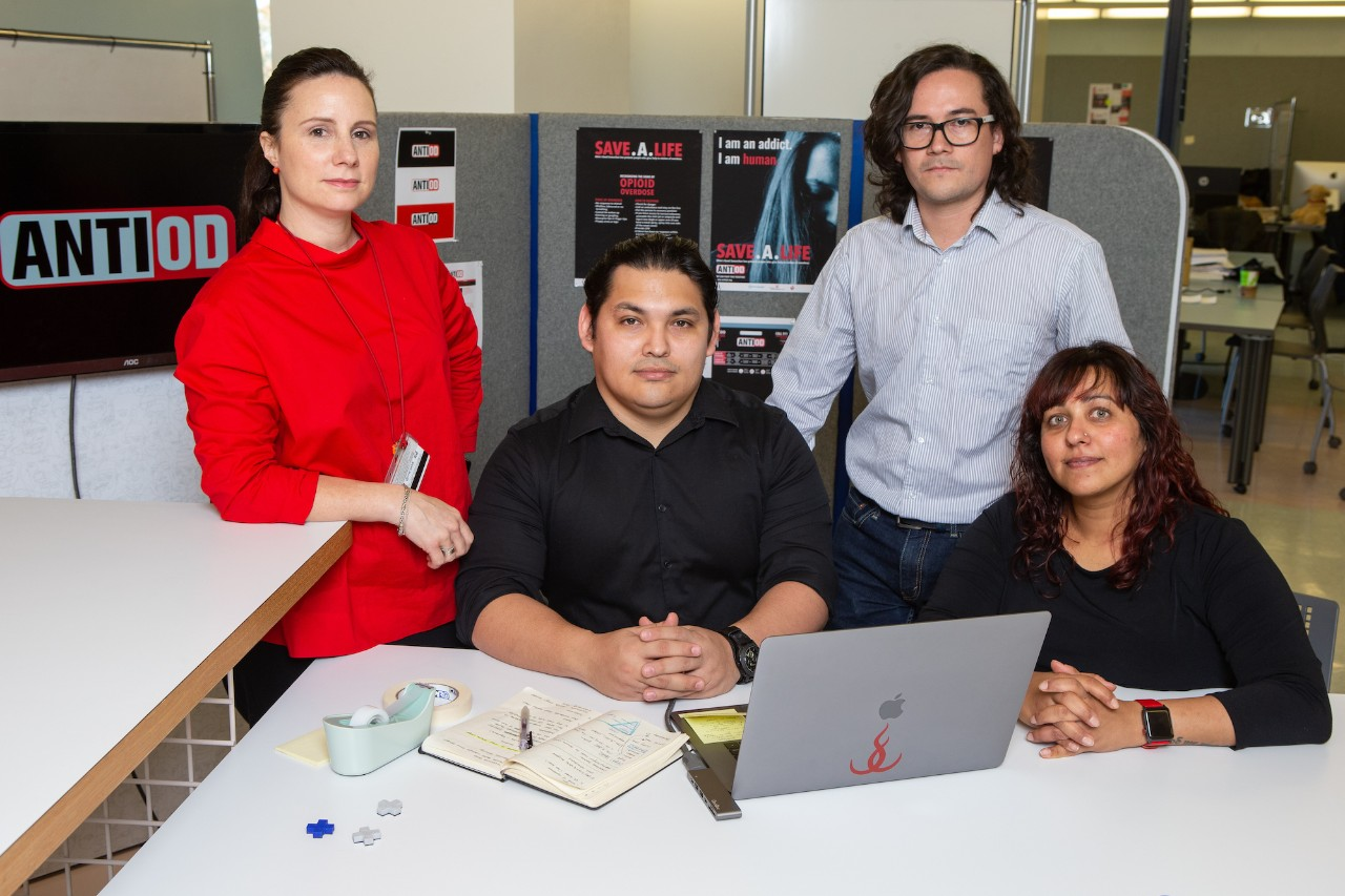 Four people pose in a design lab around a  computer and desk