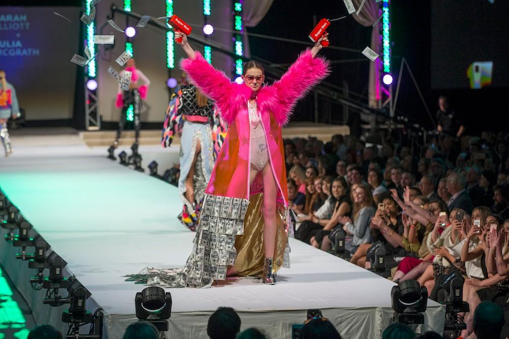 Model in pink dress shoots money guns on a fashion show runway