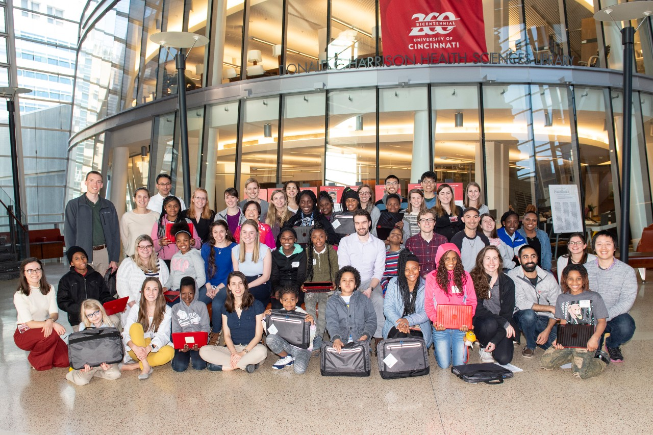 Image of twenty area schoolchildren with their medical student mentors at UC.