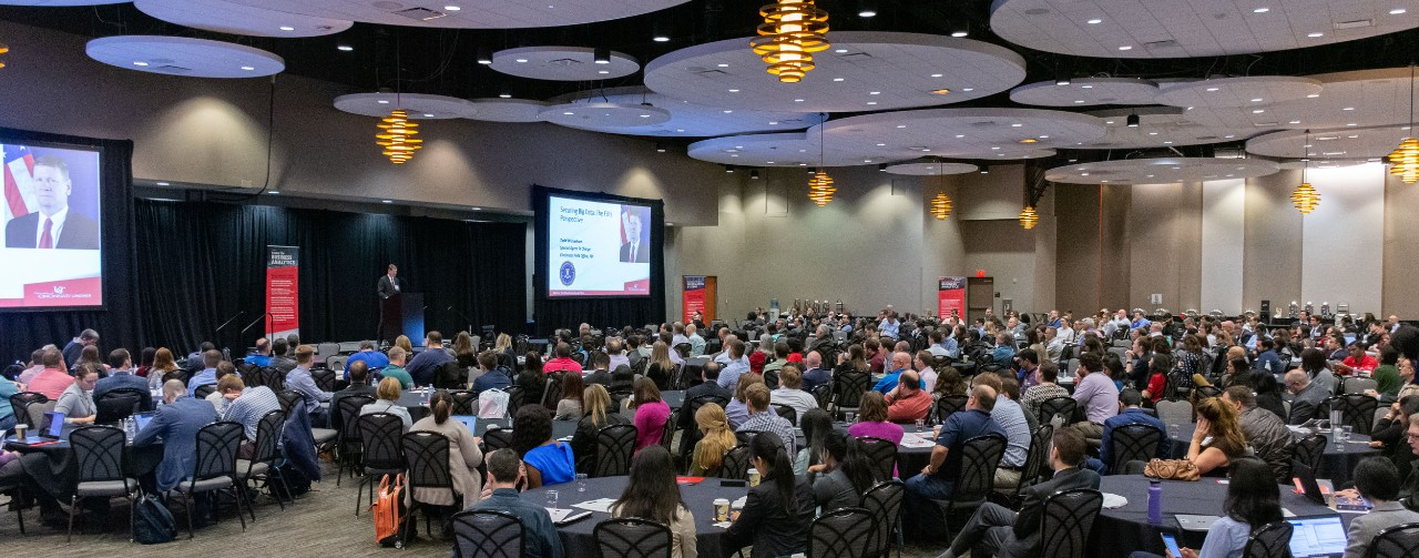 Several hundred 2019 Analytics Summit attendees sit in large conference room