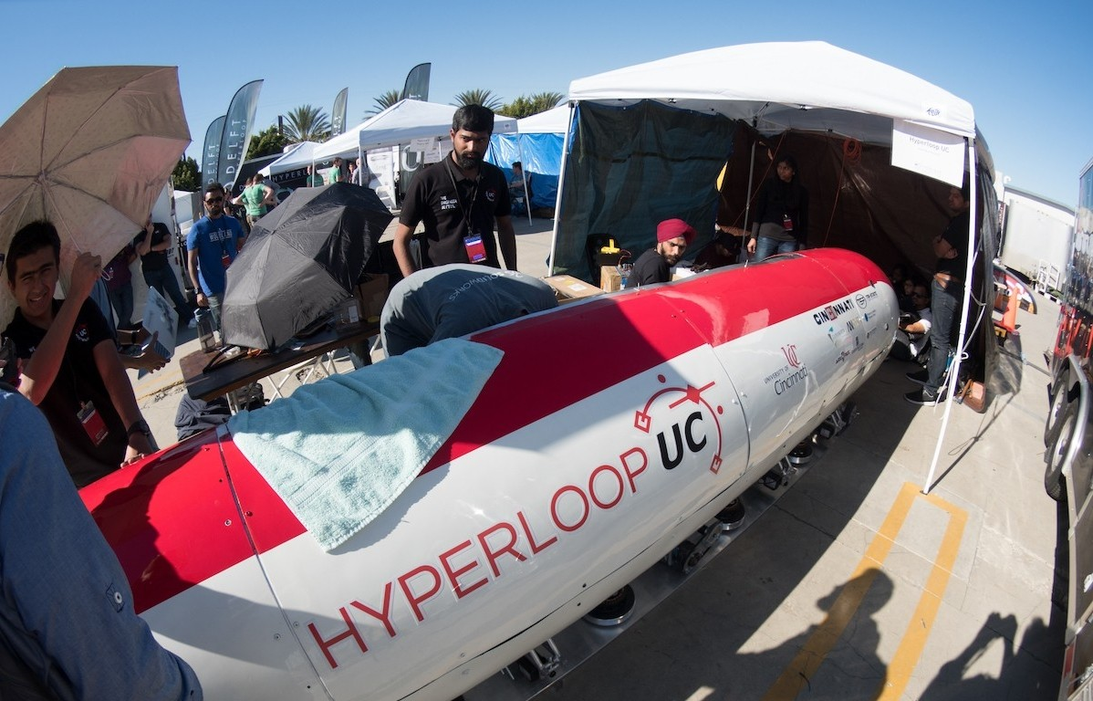 UC students huddle around a hyperloop pod in the California sun.