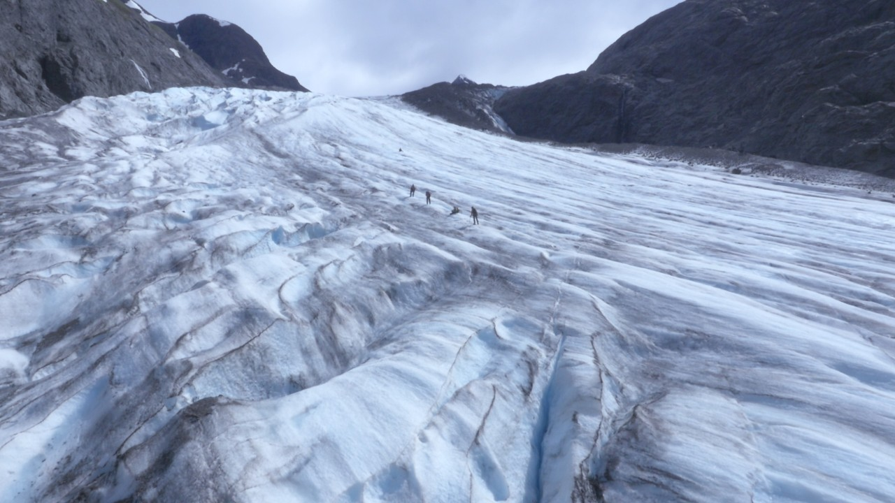 A line of racers treks across a glacier in a shot taken high above them.