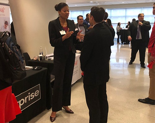 A Lindner student networks with an Enterprise representative at Dress to Impress 2019