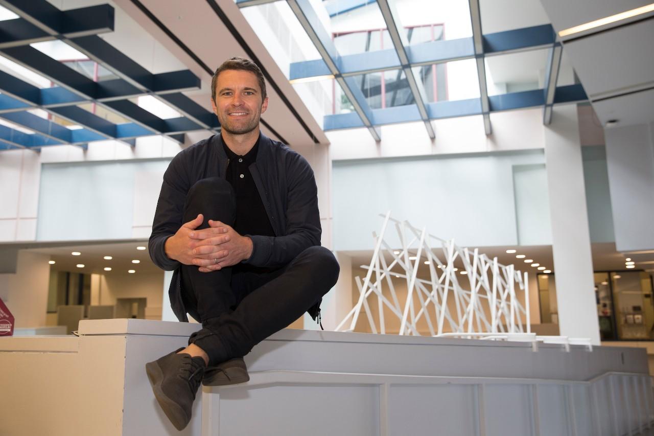 TIm Brown sits on a ledge under atrium