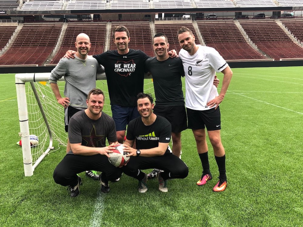 Six men pose on field with soccer ball