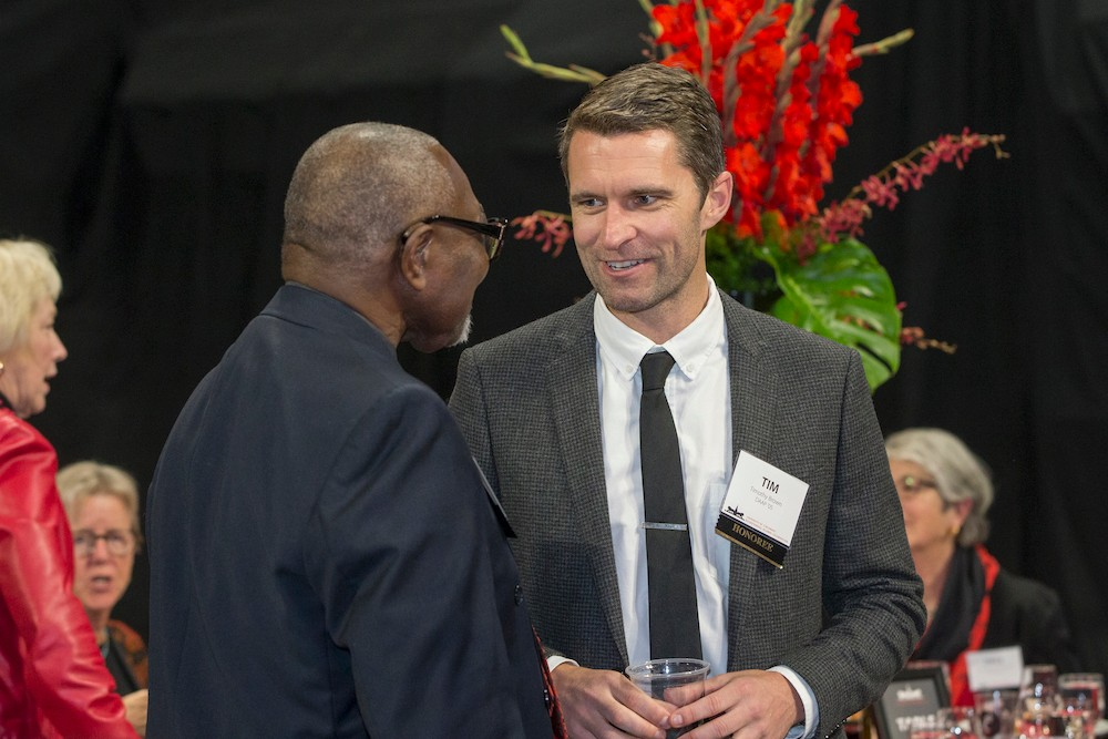 Two men chat at an event