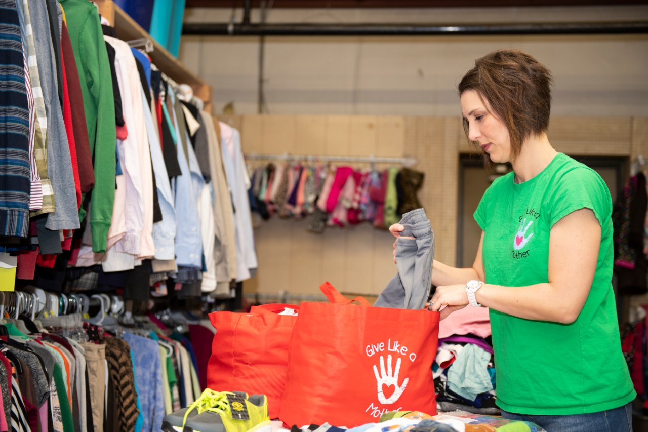 Amy Vann fills a bag with clothing and other items at the Give Like a Mother warehouse
