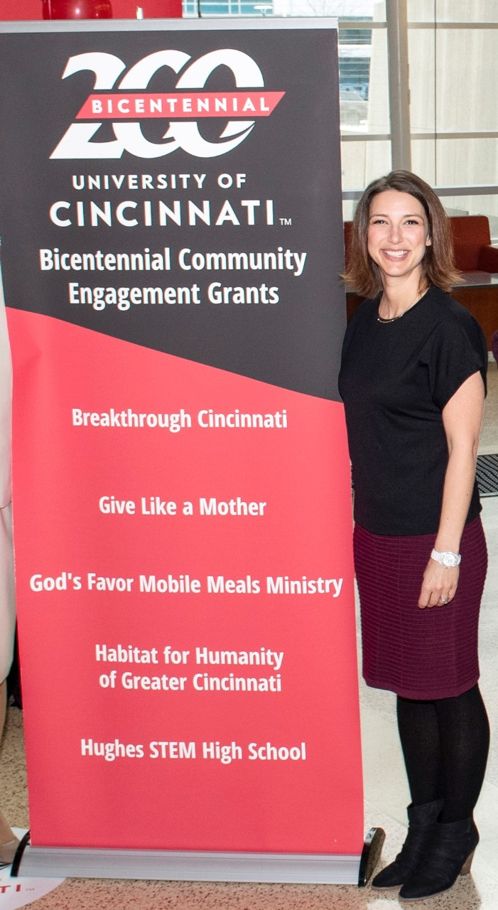 Amy Vann standing next to a banner announcing Give Like a Mother as one of UC's Bicentennial Engagement Grants
