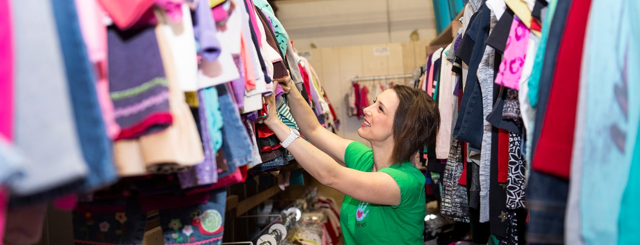 Amy Vann at the Give Like a Mother warehouse sorting through a clothing rack