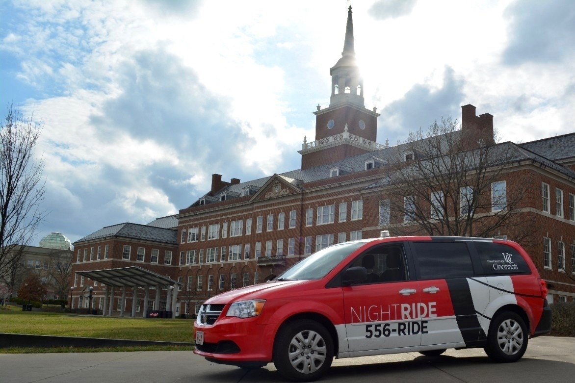 Red and white UC Night Ride van in front of McMicken Hall.