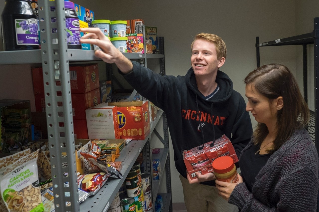 Two students reach fro food from a shelf.