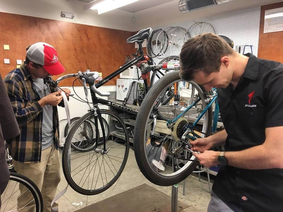 Two men work on a bicycle in a bike shop.