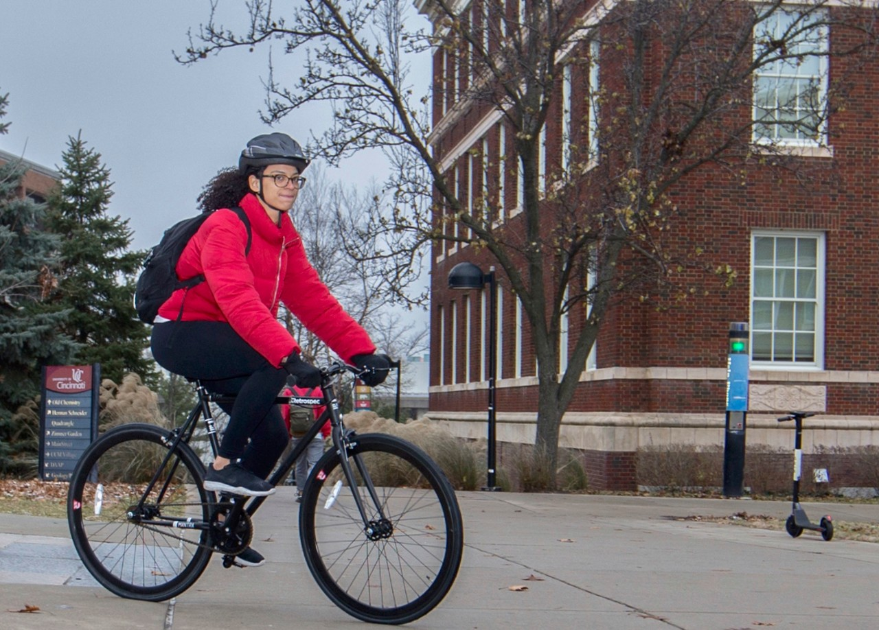 Woman rides her bike in front of UC's Old Chem building.