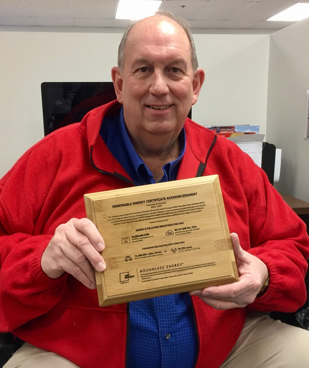Man holds a wooden plaque with energy renewal credits listed on the front.