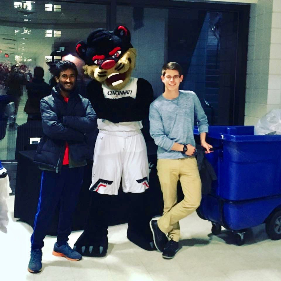 Two students stand with UC's Bearcat and a recycling can.