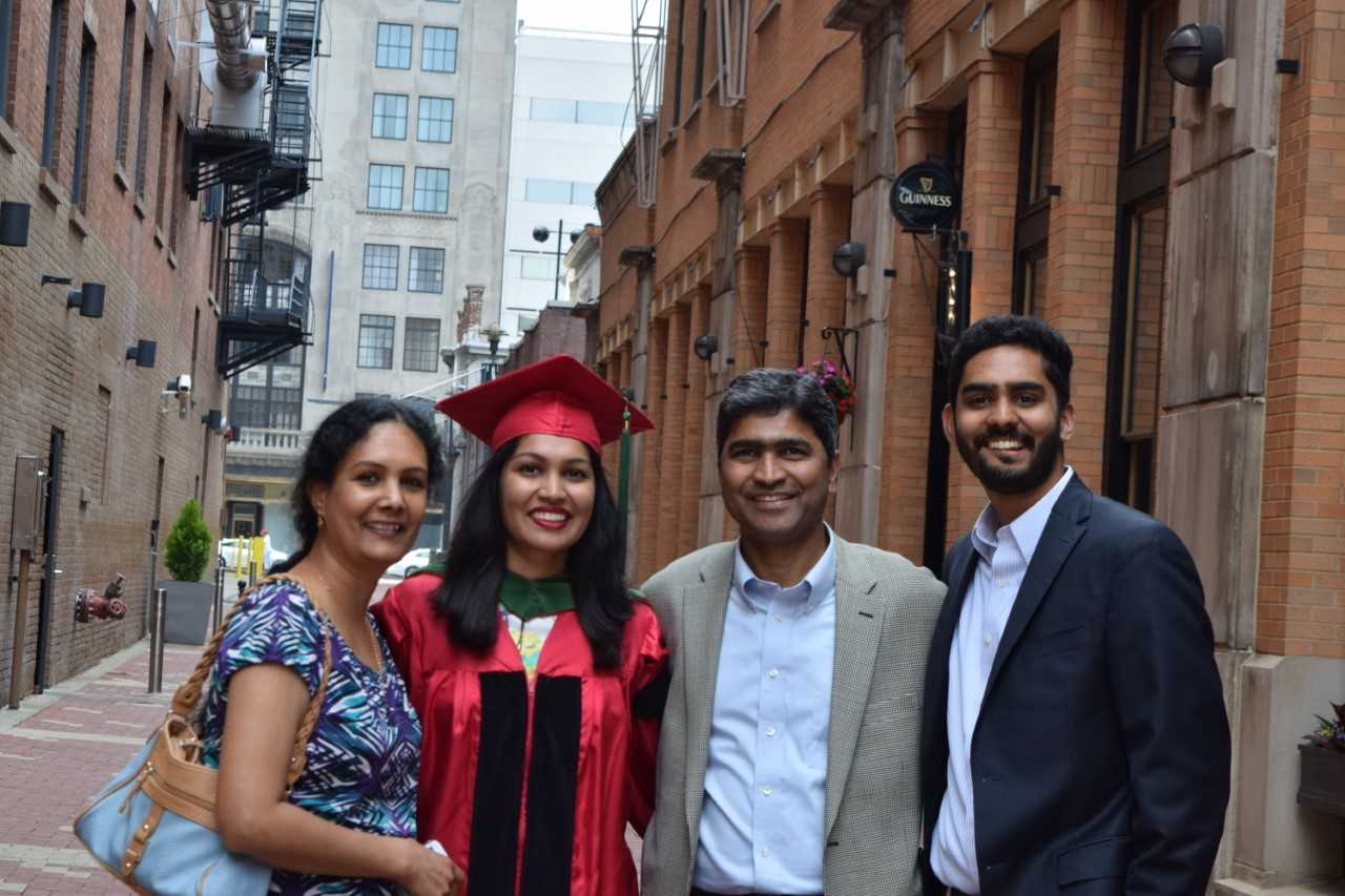 Rahul Sandella (right) is shown with his father, Rajender Sandella, sister, Namratha Sandella, and mother Padma Sandella.  Namratha Sandella is in her cap and gown. She graduated with a medical degree from the UC College of Medicine.