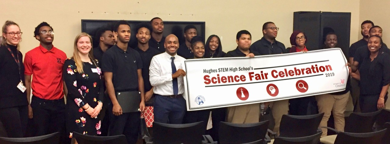 UC's Rickey Terrell and several Hughes High School students stand with their science fair celebration banner.