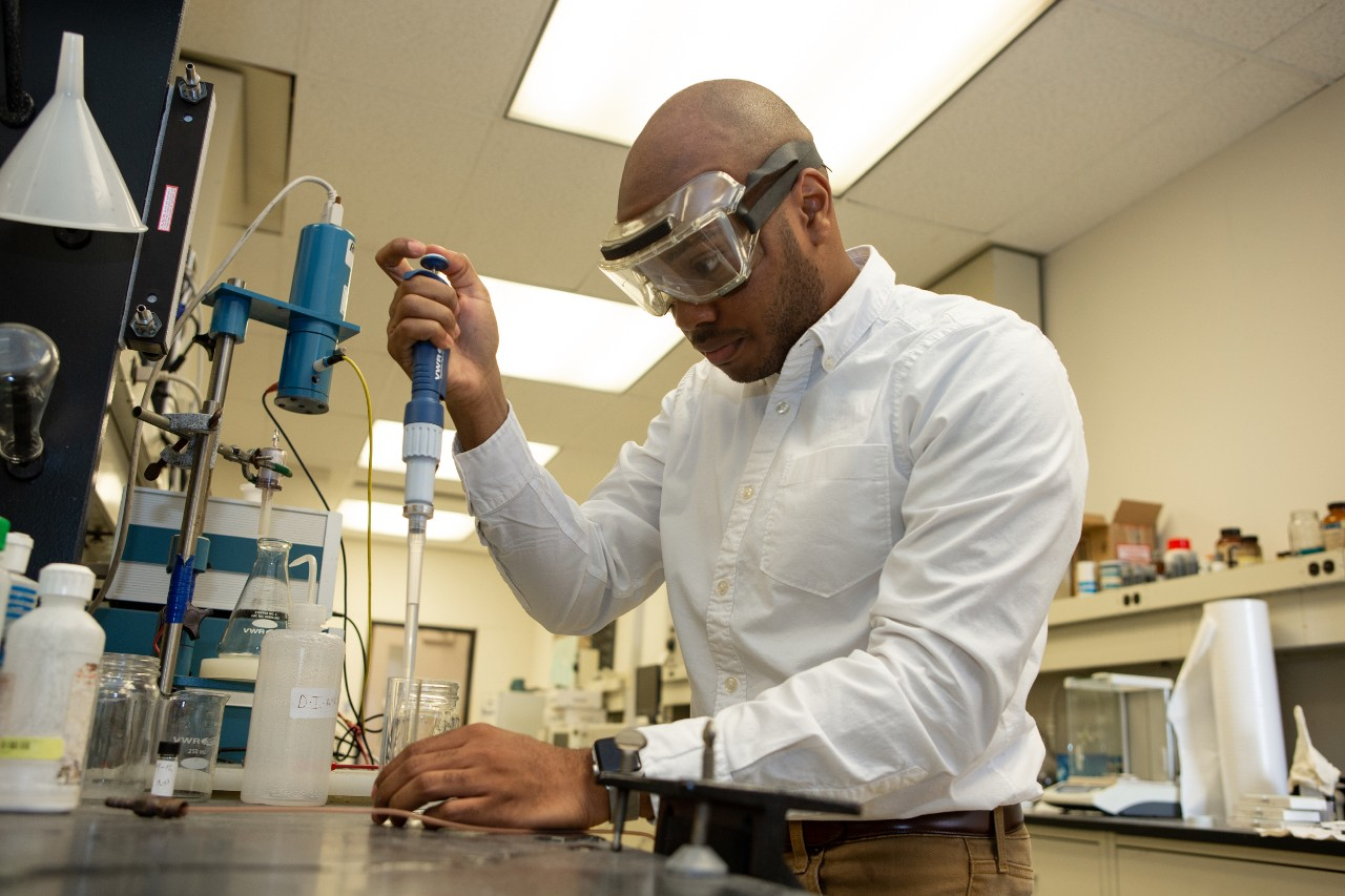 Rickey Terrell wears safety goggles as he works closely in a lab with fuel cell chemicals.