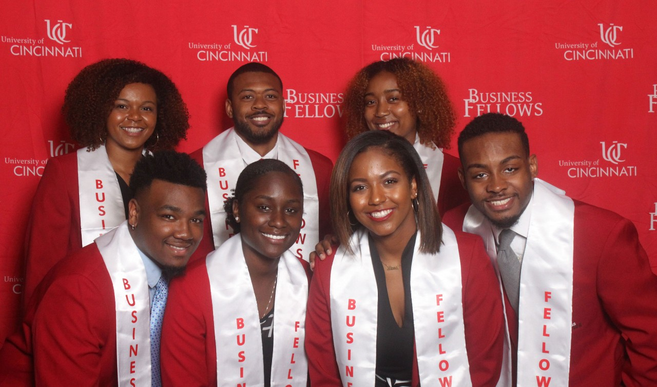 "Three young adults stand and smile behind four young adults wearing red blazers and white stoles that say ""Business Fellows"""
