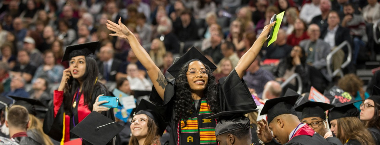 UC student holds her arms up in congratulations at a UC Commencement ceremony.